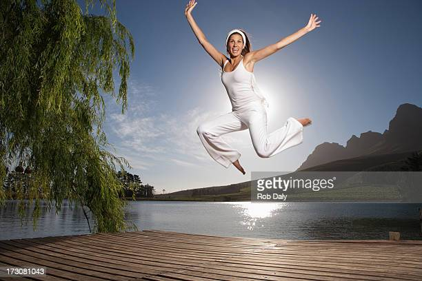 Excited woman jumping on pier