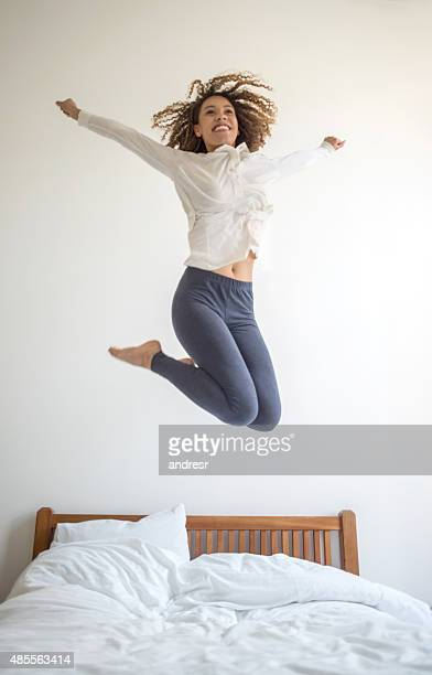 Excited woman jumping on the bed