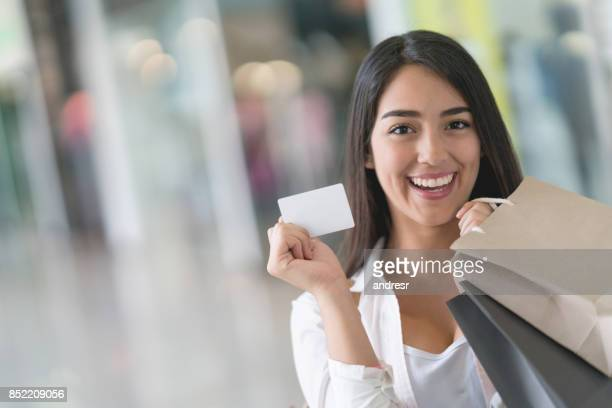 Excited woman on a shopping spree holding a loyalty card