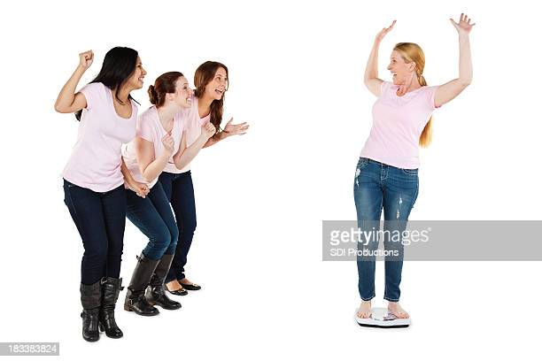 Excited Woman on Scale Being Encouraged By Her Friends