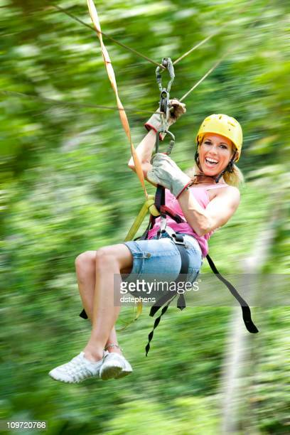 Excited woman on zipline in jungle motion blur