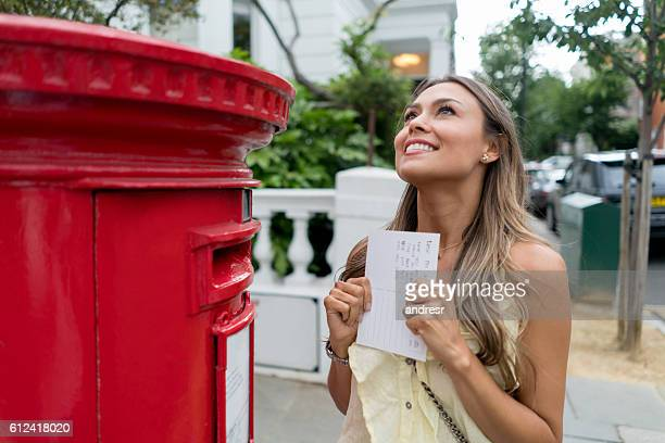 Excited woman sending a postcard