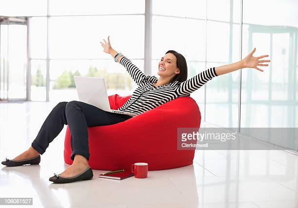 Excited woman sitting on a bean bag with laptop and arms outstretched