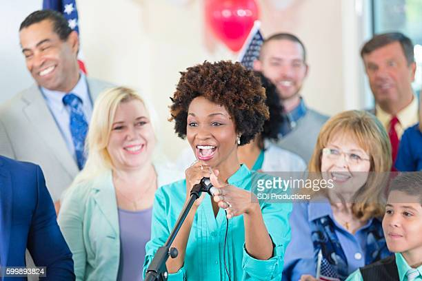 Excited woman speaking at political rally, supporting candidate