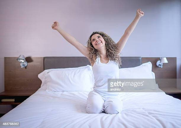 Excited woman waking up in the morning