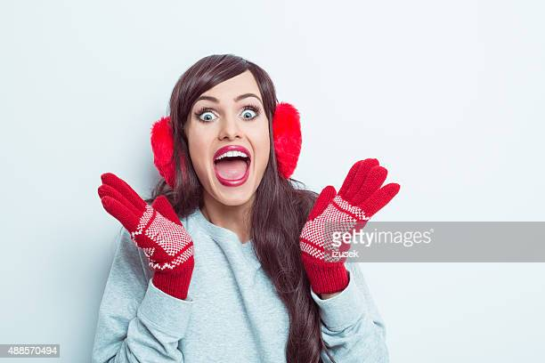Excited woman wearing red earmuffs and gloves