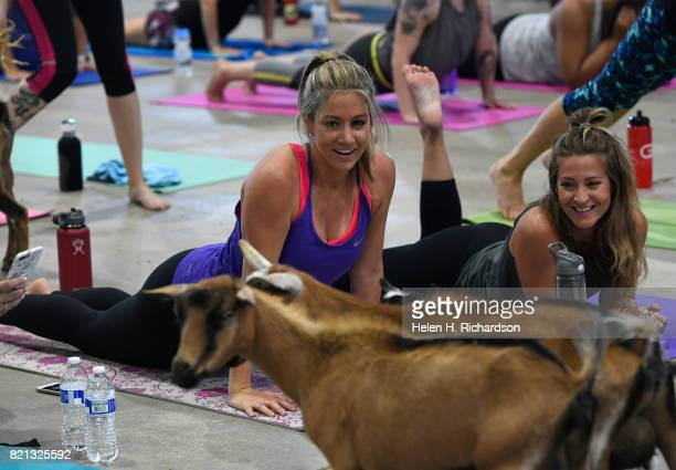 Excited yogis Liz McKenney middle and Kelly Haberer right react to the goats as they walk around the yoga floor during goat yoga at the Denver County...
