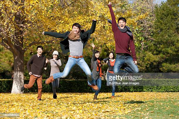 Excited young adults jumping on the lawn in autumn