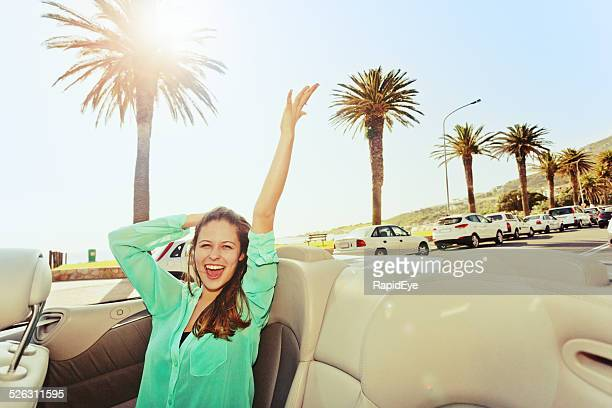 Excited young beauty rides in convertible along palm-lined promenade