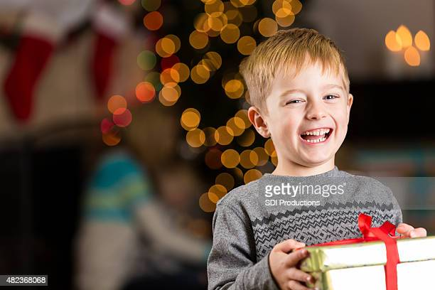 Excited young boy holding present on Christmas day