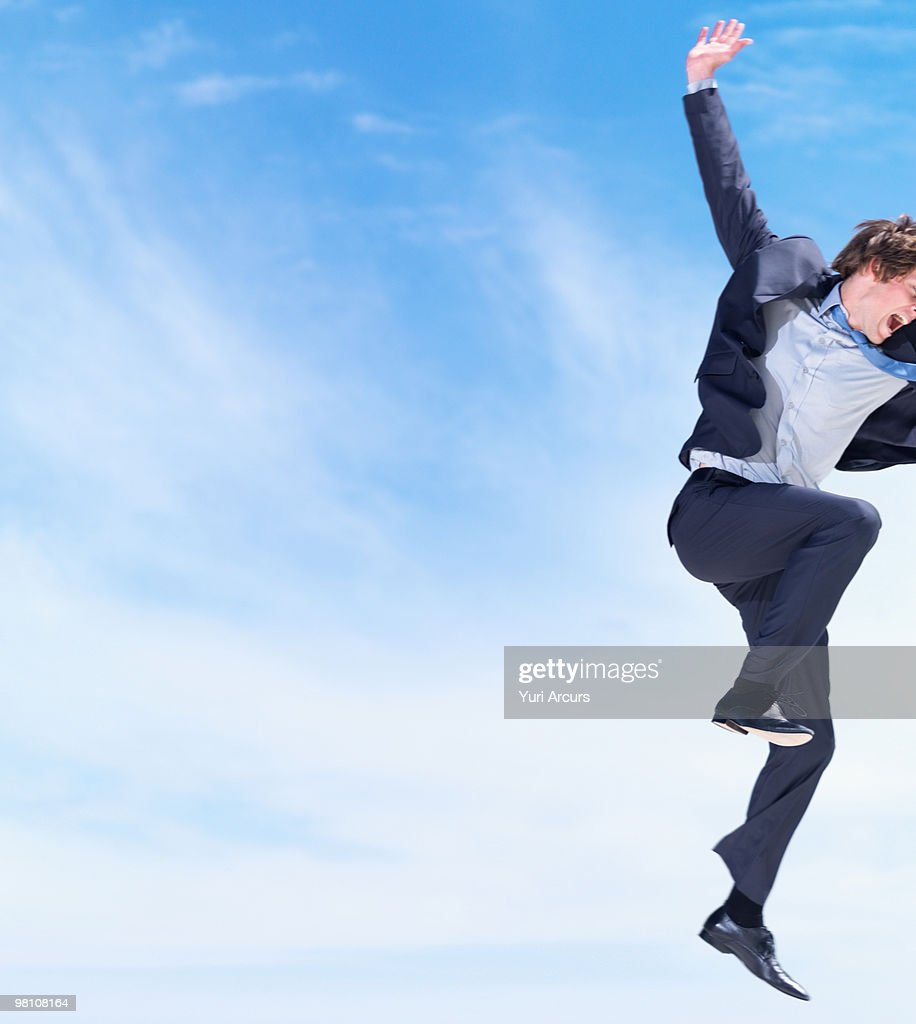 excited young business man jumping for joy stock photo