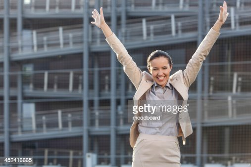 Excited young businesswoman with arms raised standing against office building : Foto de stock