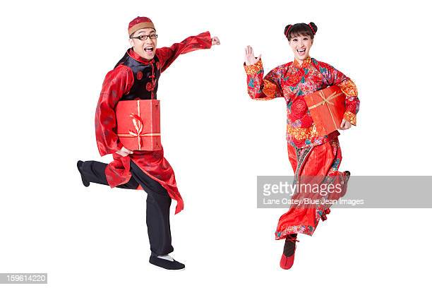 Excited young couple in traditional Chinese clothing running with gift boxes in hands