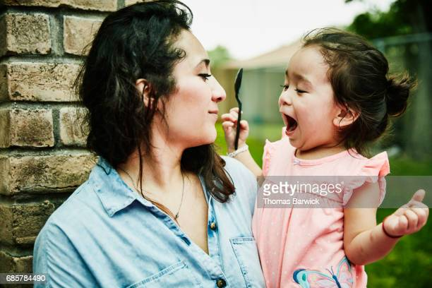 Excited young girl being held by mother during backyard birthday party