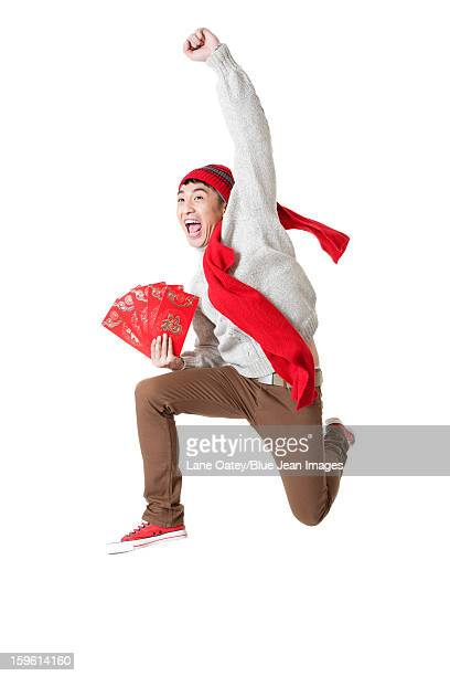 Excited young man celebrating Chinese New Year with red envelops