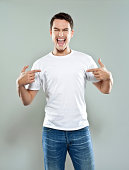 Portrait of happy young man wearing white t-shirt, pointing with fingers at his torso and laughing at camera. Studio shot, grey background.