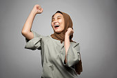 Excited young Muslim woman in white background