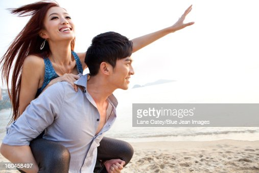 Excited young people playing piggyback on the beach of Repulse Bay, Hong Kong