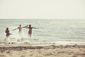 Copy space shot of three young people running into refreshing sea water.