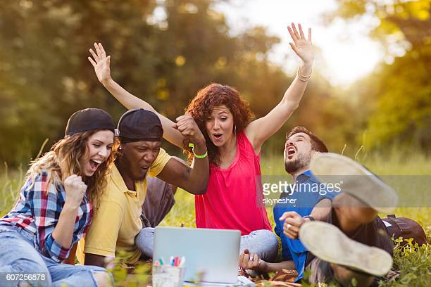 Excited young people using laptop in nature and celebrating.
