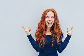 Excited young redhead woman pointing upwards towards blank copy space on a white wall with both hands and an animated expression