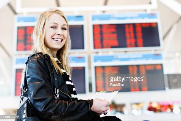 Heureux jeunes voyageurs avec carte d'embarquement dans le hall de l'aéroport