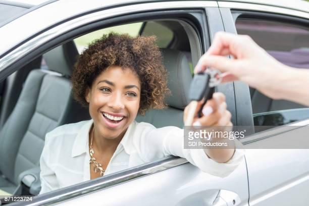 Enthousiast jonge vrouw aanvaardt nieuwe autosleutels