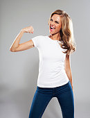 Excited young woman flexing her bicep, Studio Portrait