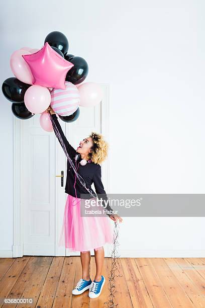 Excited young woman holding bunch of balloons indoors