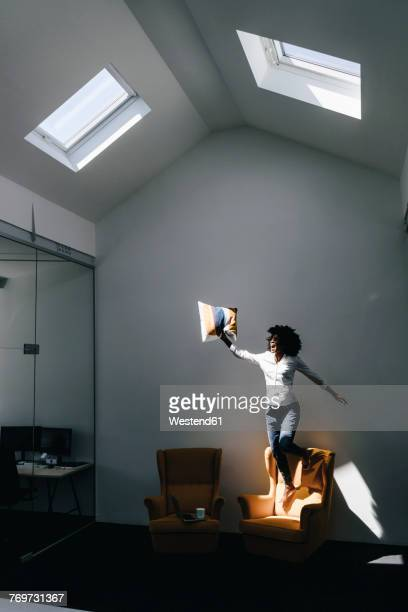 Excited young woman jumping on armchair in office