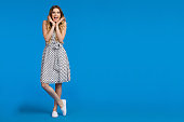 Beautiful young woman in white summer dress and sneakers is holding head in hands, shouting and looking at camera. Full length studio shot on blue background.