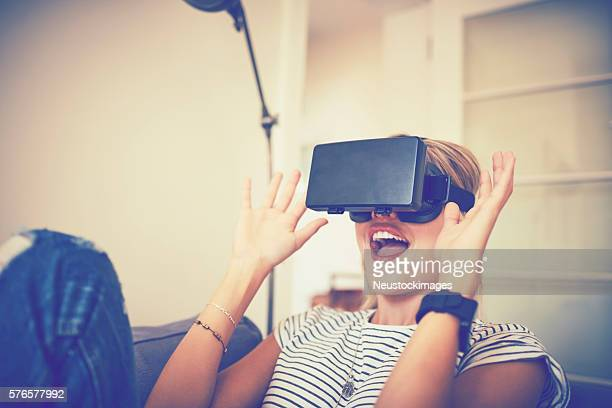Excited young woman using virtual reality headset at home
