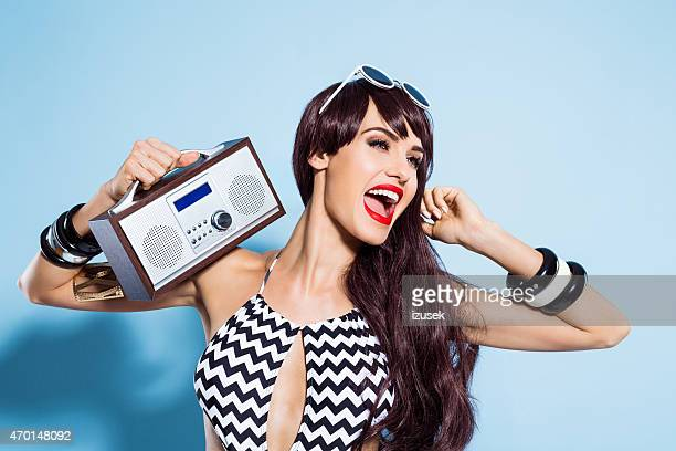 Excited young woman wearing swimsuit, listening to the radio