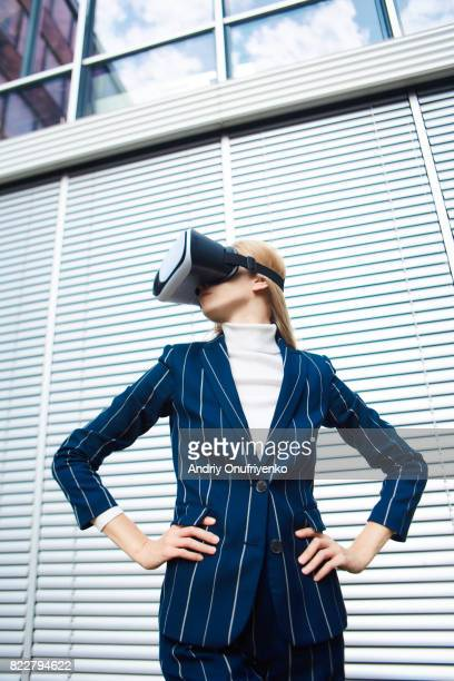 Excited young woman wearing VR glasses near office