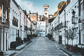 Exclusive mews with small houses on the end tower of church