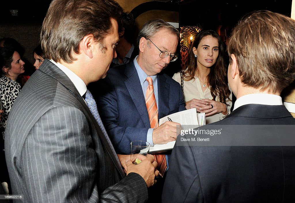 Executive Chairman of Google Eric Schmidt (2L) signs copies of his book 'The New Digital Age: Reshaping The Future Of People, Nations and Business' by Eric Schmidt and Jared Cohen, hosted by Jamie Reuben, at Loulou's on May 28, 2013 in London, England.