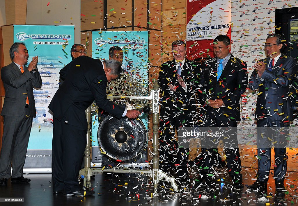Executive chairman of Westports Malaysia Holdings Bhd, G. Gnanalingam (C) hits a gong to mark the listing debut of of Malaysian port operator Westports Holdings at Malaysia Stock Exchange in Kuala Lumpur on October 18, 2013. Port operator Westports Holdings Bhd opened 8.0 percent up on its IPO price on October 18, in Malaysia's largest listing so far this year.