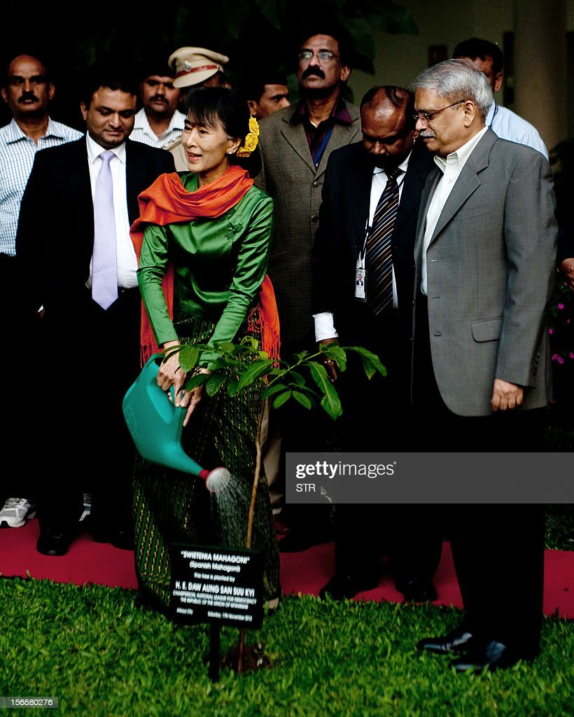 Executive Co-Chairman of Infosys Kris Gopalakrishnan (R) watches as Nobel laureate and Myanmar opposition leader and Chairperson of the National League of Democracy of Myanmar Aung San Suu Kyi waters the tree she planted during her visit to Infosys in Bangalore on November 17, 2012. Suu Kyi is on a week-long visit to India.