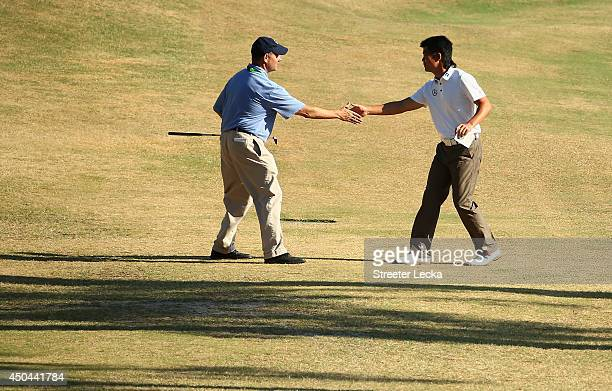 Executive Director Mike Davis shakes hands with WenChong Liang of China during a practice round prior to the start of the 114th US Open at Pinehurst...
