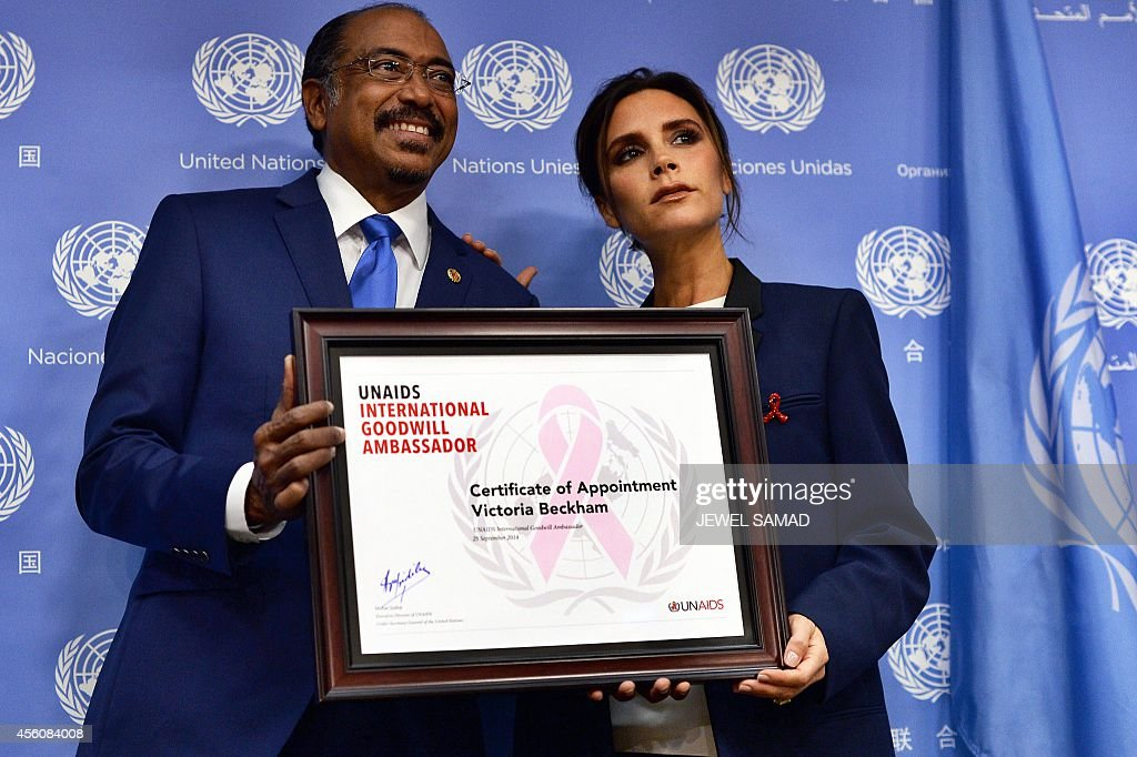 Executive Director of Joint UN Programme on HIV/AIDS Michel Sidibe presents British fashion designer Victoria Beckham with a UNAIDS international...