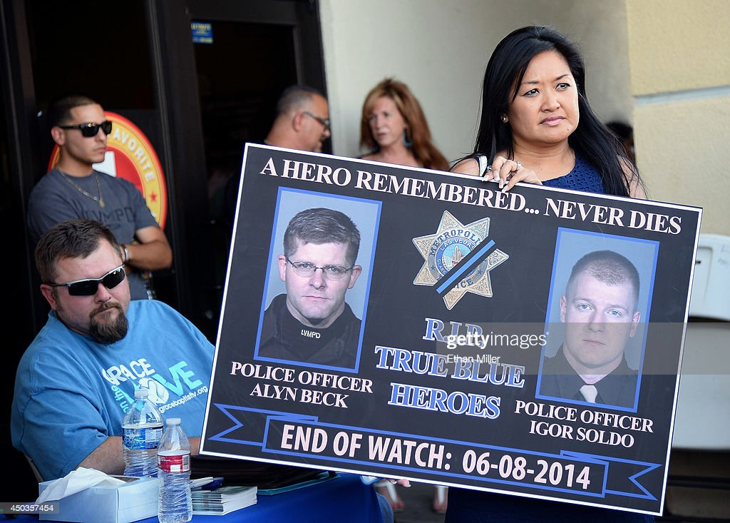 Executive Director of the Injured Police Officers Fund Minddie Lloyd holds a sign with images of the two slain police officers during a vigil outside CiCi's Pizza on June 9, 2014 in Las Vegas, Nevada. The Las Vegas Metropolitan Police Department says officers Alyn Beck and Igor Soldo were shot and killed yesterday at the restaurant by Jerad Miller and his wife Amanda Miller. Police say the Millers then went into a nearby Wal-Mart where Amanda Miller killed Joseph Wilcox before the Millers killed themselves.