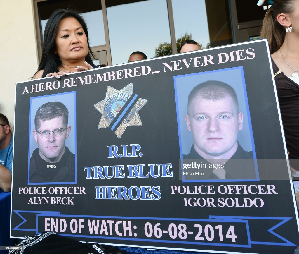Executive Director of the Injured Police Officers Fund Minddie Lloyd holds a sign with images of two slain police officers during a vigil outside CiCi's Pizza on June 9, 2014 in Las Vegas, Nevada. The Las Vegas Metropolitan Police Department says officers Alyn Beck and Igor Soldo were shot and killed yesterday at the restaurant by Jerad Miller and his wife Amanda Miller. Police say the Millers then went into a nearby Wal-Mart where Amanda Miller killed Joseph Wilcox before the Millers killed themselves.