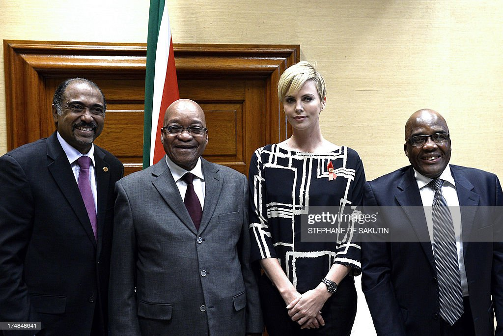 Executive Director of UNAIDS Michel Sidibe, South African President Jacob Zuma, South African-born Hollywood actress and UN Messenger of Peace Charlize Theron and South African Health Minister Aaron Motsoaledi pose for a photograph on July 29, 2013, at the Unions Building in Pretoria. Theron is accompanied by the Executive Director of UNAIDS Michel Sidibe to discuss the strides being made in the fight against HIV and AIDS and how collaboration can assist mitigate the pandemic's negative impact on young girls. They will also explore ways to support South Africa's efforts to enable young women and girls to lead healthier HIV and AIDS-free lives.