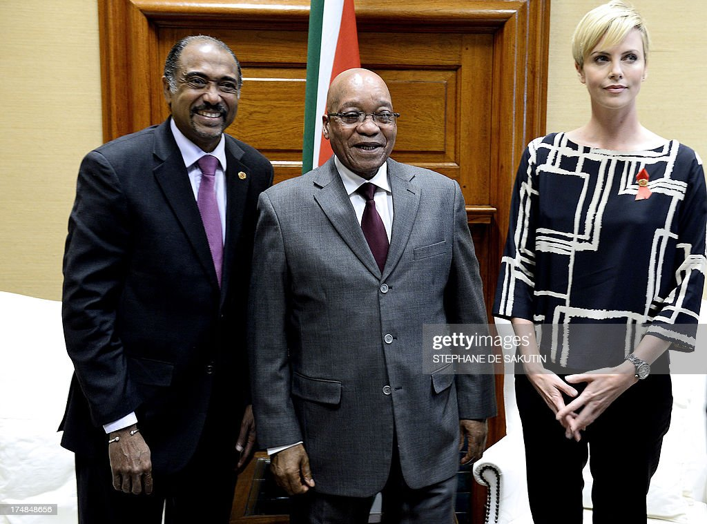 Executive Director of UNAIDS Michel Sidibe, South African President Jacob Zuma, and South African-born Hollywood actress and UN Messenger of Peace Charlize Theron pose for a photograph on July 29, 2013, at the Unions Building in Pretoria. Theron is accompanied by the Executive Director of UNAIDS Michel Sidibe to discuss the strides being made in the fight against HIV and AIDS and how collaboration can assist mitigate the pandemic's negative impact on young girls. They will also explore ways to support South Africa's efforts to enable young women and girls to lead healthier HIV and AIDS-free lives. AFP PHOTO / STEPHANE DE SAKUTIN
