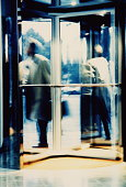 Executive in revolving door (blurred motion)
