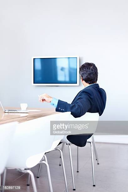 Executive looking at television in a conference room
