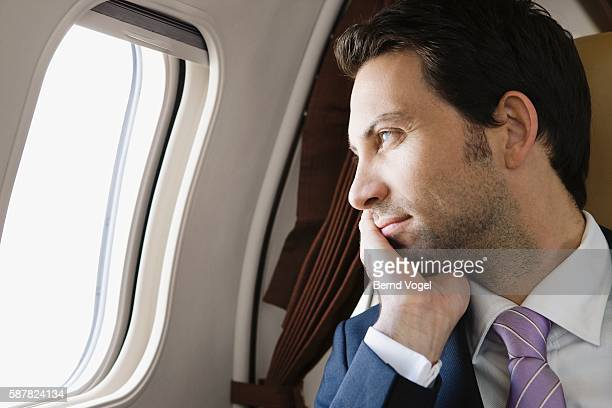 Executive looking out of airplane window