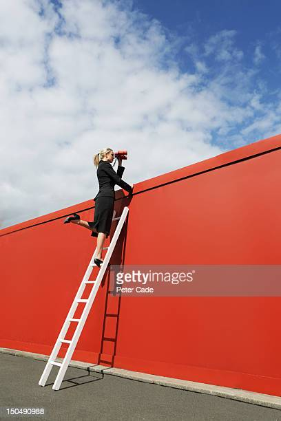 Executive looking over red wall with binoculars