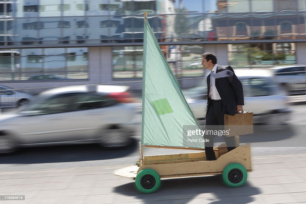 Executive on kart with sail riding along street : Stock Photo