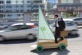 Executive on kart with sail riding along street